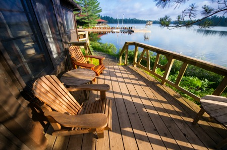 two chairs sitting in a deck near the water