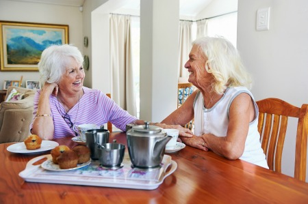 two women with silver hair sitting at a table having tea and laughing