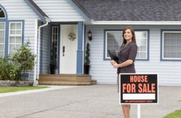 real estate agent beside a home for sale sign