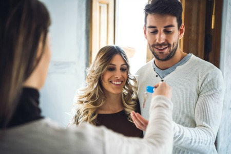 smiling man and woman accepting keys from real estate agent for new house