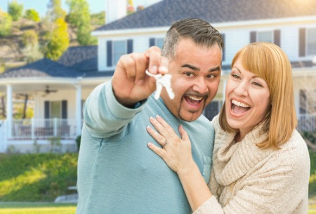 man and woman smiling and holding house keys