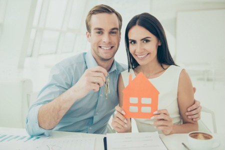 woman and man smiling and holding keys and a house cut out