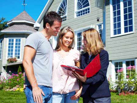 real estate agent with couple buying a home